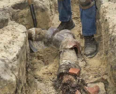 Man digging up a homes damaged sewer pipe