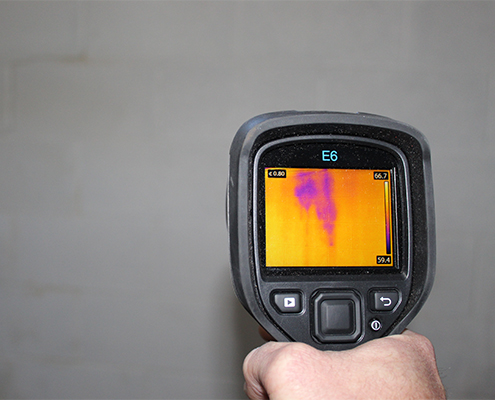Inspector using an infrared camera to view hidden moisture in a wall