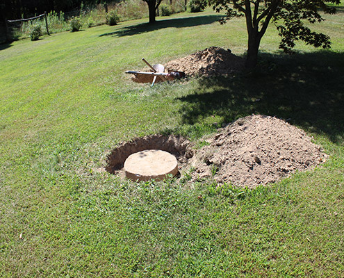 Green lawn with holes dug to expose septic tank lids during a septic inspection