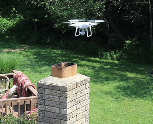 Drone flying around a rooftop chimney during a home inspection