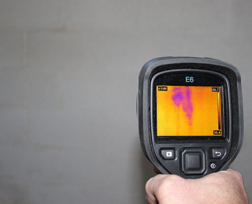 Inspector using an infrared camera to detect unseen moisture in a wall